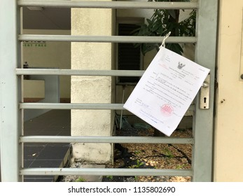 July 10, 2018 Bangkok. A Subpoena hanging in front of the house. Because the owner didn't payment his mortgage to the bank.