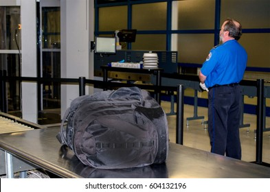 July 14, 2014, USA; A TSA worker stands by while an unattended bag waits to be claimed at an America  airport