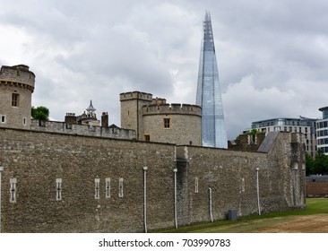 July 15, 2017 - London, England: The exterior wall of the Tower of London with the Shard in the background on a cloudy day