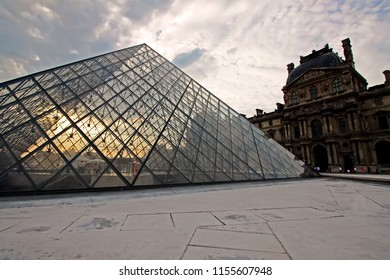 July 18, 2017 - Paris, France :: The sunset scene with cloudy sky over the glass pyramid of Louvre Museum in Paris, France