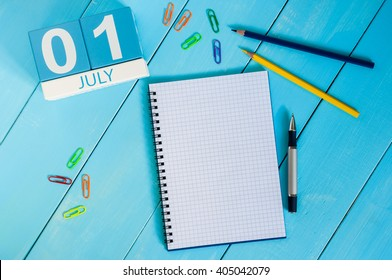July 1st. Image of july 1 wooden color calendar on blue background. Summer day. Empty space for text
