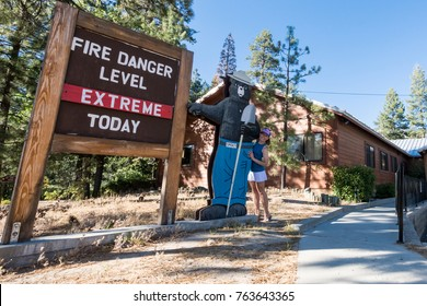 JULY 2 2017 - Idyllwild, CA: Adult female poses with a Smokey the Bear sign by ranger station indicating the fire danger is Extreme on a hot summer July day in the  San Bernardino National Forest