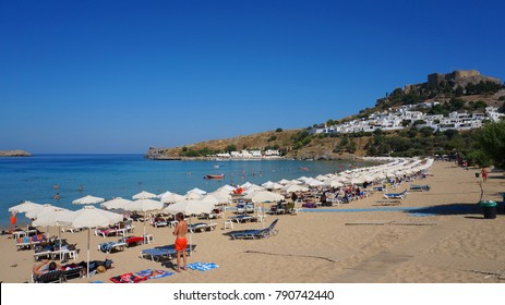 July 2014: Photo from iconic picturesque beach near village of Lindos with ancient Acropolis overlooking the Aegean and turquoise clear water seascape, Rhodes island, Greece