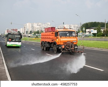 """July 2016, Moscow, Russia. Watering machine during extreme heat. In a watering machine the name of the company GBU """"Highways"""". The red sign on the bus behind the windscreen - the Foreman of the route"""