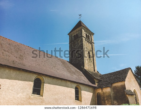 July 21, 2017. France. Region Burgundy. An old stone church with a tower, a bell tower on which is a cross and a rooster, next to an old cemetery in a French village in the summer on a sunny day.