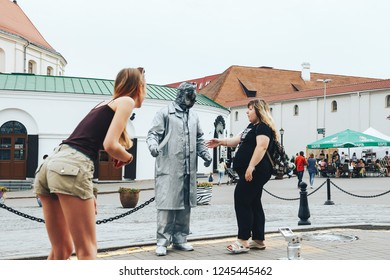 July 21, 2018 , Minsk,Belarus Street walks Two women stand near a man in a stone suit