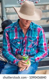 JULY 22, 2017 NORWOOD COLORADO - cowboy in plaid shirt watches San Miguel Basin Rodeo, San Miguel County Fairgrounds