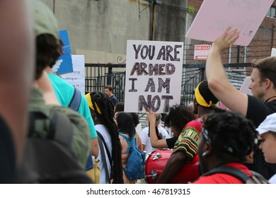 """July 26th, 2016 Philadelphia, PA: Democratic National Convention - A sign is held up in front of police that reads """"You Are Armed I Am Not"""" during a Black Lives Matter March"""