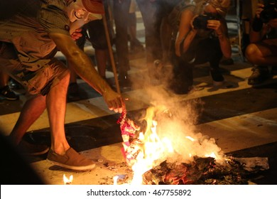 July 27th, 2016 Philadelphia, PA: Democratic National Convention - A man wearing a Guy Fawkes mask plays and dances around an American Flag he just lit on fire outside Wells Fargo arena