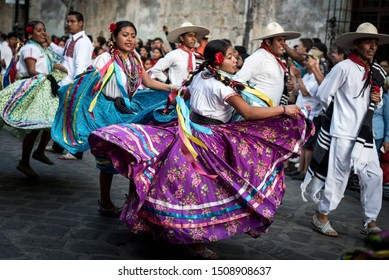 July 28, 2019: Beautiful dancers in colorful traditional dresses dancing during the Guelaguetza parade in Oaxaca, Mexico