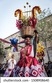 July 28, 2019: A 'china oaxaque–a' dances balancing a basket with flowers on her head during the Guelaguetza parade in Oaxaca, Mexico