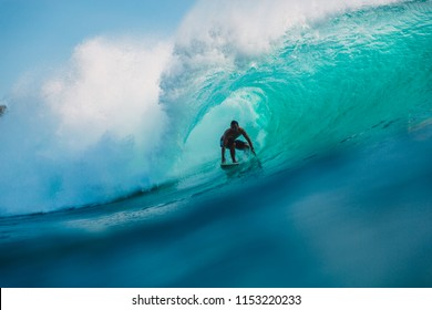 July 29, 2018. Bali, Indonesia. Surfer ride on barrel wave. Professional surfing in ocean at big waves