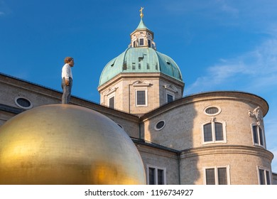 July 29, 2018. Figure of a man standing on a golden ball in front of the Salzburg Cathedral, Kapitelplatz Square in the historic centre of Salzburg Austria.
