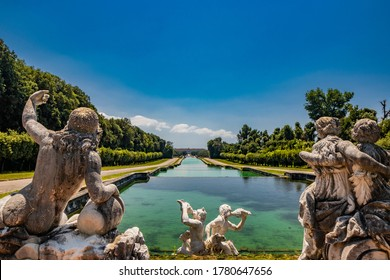 July 3, 2020 - Royal Palace of (Reggia di) Caserta - The very long basin of the park's artificial lake. The perspective view. The marble statues look and extend their hand towards the palace. Blue sky