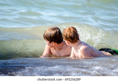 July 30 2017, Michigan USA, two boys on beach  brace for the oncoming wave that is getting to wash over them while they play at the Warren Dunes state park
