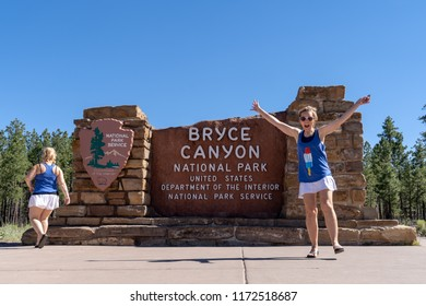 JULY 4 2018 - BRYCE CANYON, UTAH: Two adult females pose in a silly goofy fun manner at the Bryce Canyon National Park sign. Concept for friends travel, summer road trips