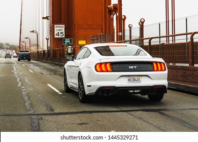 July 4, 2019 San Francisco / CA / USA - White Ford GT Mustang travelling on Golden Gate Bridge; rear view
