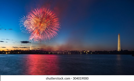 The July 4 fireworks at Washington DC. View from the Jefferson Memorial grounds. The Tidal Basin waters are in the foreground and the Washington Monument to the right. Photograph shot on July 4, 2014