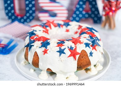 July 4th bundt cake covered with a vanilla glaze and decorated with chocolate stars on a white plate.