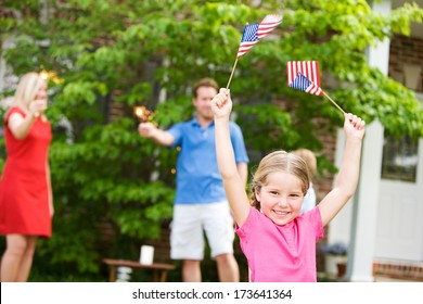 July 4th: Excited Little Girl Holding Flags in the Air