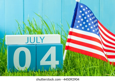 July 4th. Image of july 4 wooden color calendar on blue background with flag of the USA. Summer day. Independence Day Of America