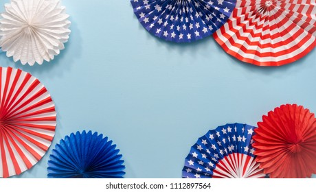 July 4th theme paper fans on blue background.