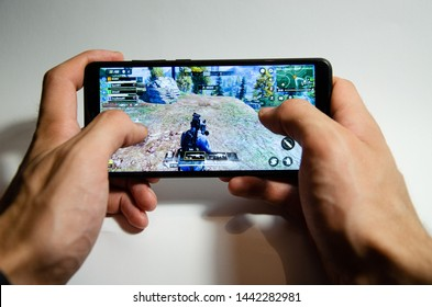 July 5, 2019. USA, Los Angeles.  Hands holding a smartphone with a game of Call of Duty Mobile. Gameplay game, first person, on white background