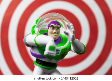 JULY 7 2019: Buzz Lightyear in an action pose from the Toy Story movie franchise with red ring background illustrating his laser beam feature - Disney action figure
