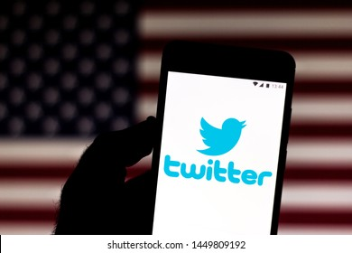 July 9, 2019, Brazil. In this photo illustration the Twitter logo is displayed on a smartphone. In the background, flag of the United States of America.