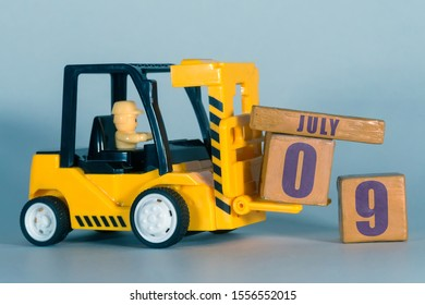 july 9th. Day 9 of month,  Construction or warehouse calendar. Yellow toy forklift load wood cubes with date. Work planning and time management. summer month, day of the year concept.