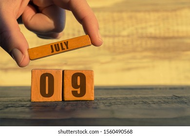 july 9th. Day 9 of month, calendar on a wooden cube. a woman's hand puts the name of the month on the number of the month on a wooden background summer, day of the year concept.