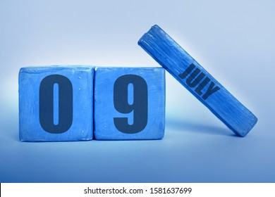 july 9th. Day 9 of month, Handmade wood cube calendar with date month and day in trendy classic blue color of the year summer month, day of the year concept