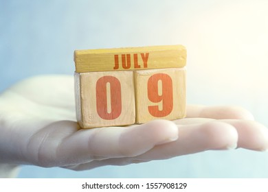 july 9th. Day 9 of month,Handmade wood cube with date month and day on female palm summer month, day of the year concept