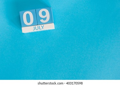 July 9th. Image of july 9 wooden color calendar on blue background. Summer day. Empty space for text