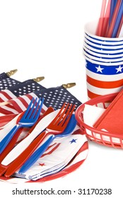 July fourth patriotic utensils including plastic forks, knives; spoons, napkins, plates and cups on a white background.