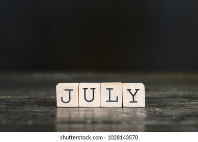 July. Wooden cube letters on the black table.