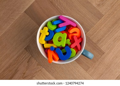 Jumble of colourful plastic lettering in a mug spelling word Tax