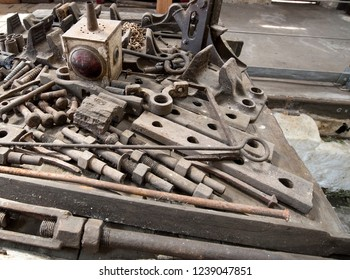Jumble of old rusting iron spare parts on a workshop bench