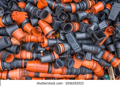 Jumble of orange and black plastic plant pots