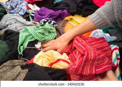 Jumble sale market stall with female hands rummaging
