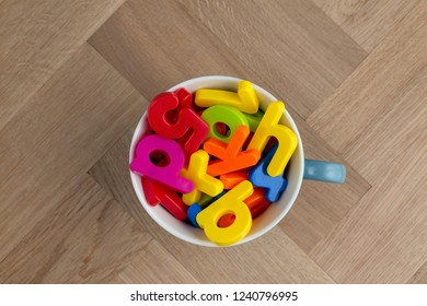 Jumble of toy colourful lettering filling on grey mug sitting on a wooden floor