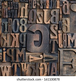 Jumbled arrangement of different sized wooden printers typeface letters of the alphabet forming a background pattern