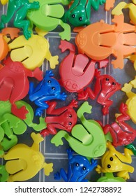 Jumbled array of red green blue and yellow plastic toy frogs laid out on flat tabletop