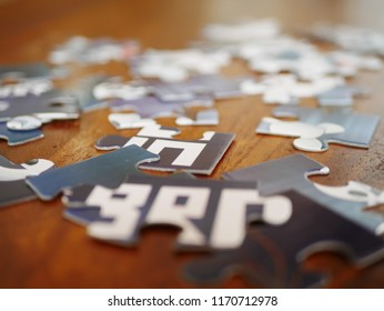 Jumbled blue and white jigsaw puzzle pieces on wooden table