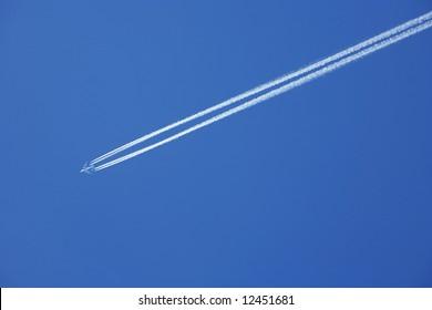 a jumbo jet flies across a blue sky leaving vapour trails