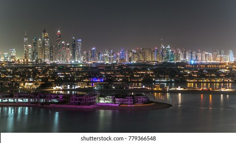 Jumeirah Palm island night timelapse in Dubai, UAE. Jumeirah Palm is artificial and unique island in Dubai with skyscrappers on the background. Villas top view from atlantis