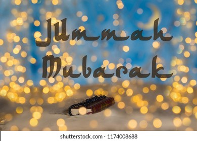 Jummah Mubarak! - Blessed Friday! Quran and praying beads. Closeup. Night lights bokeh background