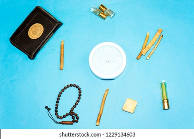 jummah mubarak time, holy book of muslims and rosary, siwak, perfume on blue background