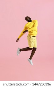 Jump. Happy black man jumping in air and laughing on pink background. Full length portrait of cheerful smiling male model in yellow fashion clothes having fun, studio shot