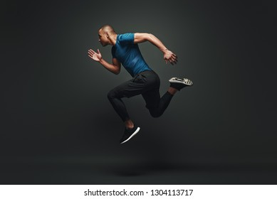 Jump higher! Sportsman jumping over dark background